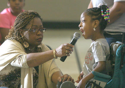 A'Marria Linton of the Holy Rosary Church Youth for Christ sings as Angela Linton holds the microphone.