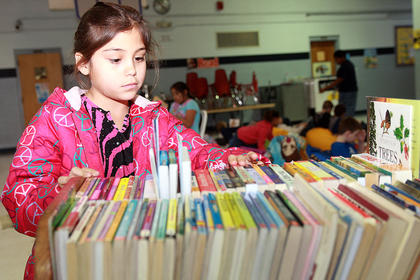 Sara Cepeda looks for a book to read on one of the carts available to the students.