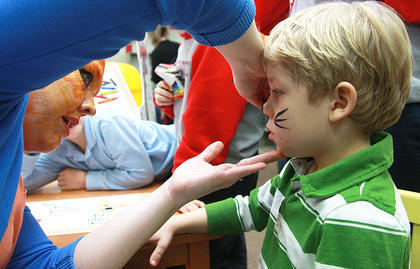 "Library Director Amy Morgeson, dressed as the fish from ""The Cat in the Hat,"" paints cat whiskers on Gabriel Mullins, 4."