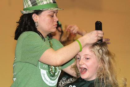 One of the volunteer barbers, Taylor Claypool, goes to work cutting 8-year-old Anna Spalding's hair.