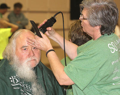 Stephen Norris may look sad as his head and beard are shaved by volunteer Vickie Childers, but he's anything but. After going bald for the cause, Norris said he did it because he wanted to help the kids.