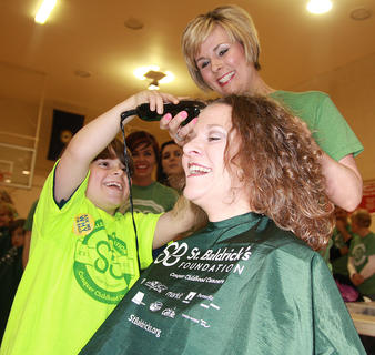 Enterprise Publisher Stevie Lowery is the first shavee at this year's St. Baldrick's event. Her son, Owen, takes the first few swipes at her head with some help from stylist Nicole Thompson.