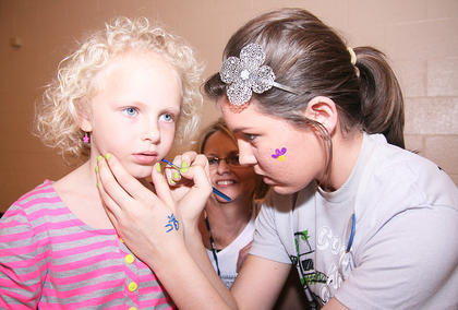 Olivia Mattingly, 5, has her face painted by Sarah Abell. Olivia&#039;s grandmother, Sandy Thompson, watches in the background.
