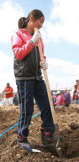 Yuka Kato, 12, digs a hole for a seedling.