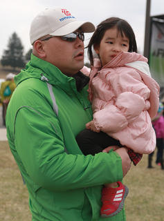 Masato Kubayashi and his daughter, Yuno, 3, wait for tree-planting to begin.