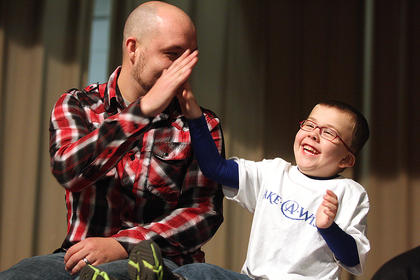 Gage Phillips, this year's Make-a-Wish child, gives his father, Dustin, a high five during Saturday's event. Gage's wish is to go to Walt Disney World Resort and meet Minnie Mouse. Gage was diagnosed with epilepsy, and born with a heart condition that makes pumping blood difficult.