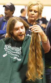 Shawn Medley of the team It's a Family Off-Hair seemed impressed with the first of his two donations to Locks of Love.