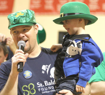 Emcee Jim Reed holds Landon Thompson, the 2011 St. Baldrick's ambassador child, who returned for this year's event. Thompson was diagnosed with bilateral retinoblastoma, but it now doing well.