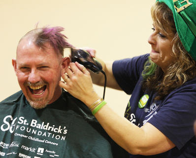 Tom Robey of the team It's a Family Off-Hair can't help laughing as he has his head shaved by Kim Childers.