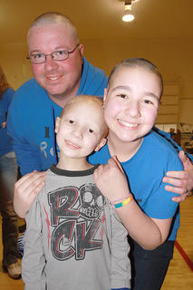 Alex O'Bryan, 13, of Bardstown is pictured with her brother, Joe Charles, 7, who is undergoing treatment for brain cancer. Their father, Jason, also shaved his head.