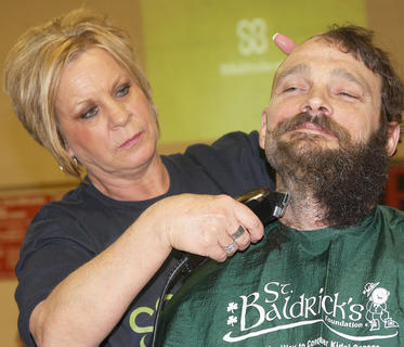 Shane Dozier sits as Carol Curtsinger shaves his head and beard.
