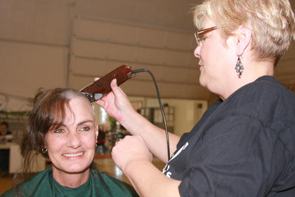 Sheila Moore of the team Casper and the Looneytunes sits for a haircut from stylist Connie Smith. Moore is one of seven siblings who shaved their heads in honor of their sister, Sue Beavers, who is undergoing treatments for non-small cell lung cancer.