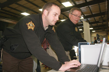 Deputy Courtney Deering and Sheriff Jimmy Clements collected fingerprints and took pictures to make Kid Print ID cards at the Farm, Home and Garden Show.
