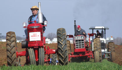 Pat Maupin (straw hat) leads a procession of tractors on a pass through the field.