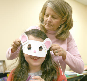 "Beth Overgauw helps Savannah Chapman with the mask she created for her role in ""The Lion and the Mouse."" Kentucky Classic Theatre hosted an arts camp for aspiring young actors during Spring Break at Centre Square and Angelic Hall. Beth Overgauw led the classes for the younger students, while G.B. Dixon, Nathan Allen and Chris Lito Tamez provided lessons for the older students."
