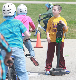 Doug Beckhart of Kosair Children's Hospital visited Lebanon Elementary School on April 9 for a bike rodeo. Throughout the day, Beckhart taught students bike safety, including wearing a helmet, stopping at stop signs, obeying traffic signals and safely crossing railroad tracks. Gavin Bardin was in charge of the traffic light while Crystal Edlin's fourth graders went through the bike rodeo course.