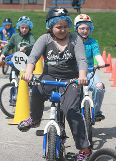 Grace Magana (front), Scott McCarty (blue shirt),  and Cameron Lanham (green shirt) ride their bikes through the course.