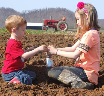 Andrew, 3, and Addie Buckman, 9, enjoys playing in the freshly plowed soil.
