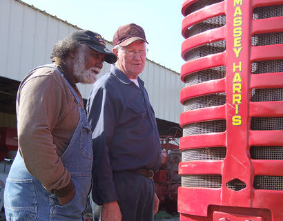 Percy Ridgeway, left, and Glen Powell take a look at and discuss Jim Browning's 1951 Massey Harris tractor.