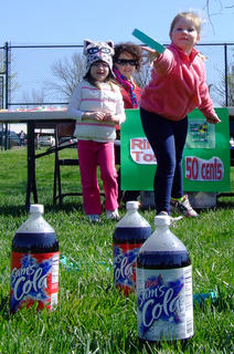 Madison Honaker, 6, tries the ring toss game as her cousin, Raley Joe Gordon, 4, watches.