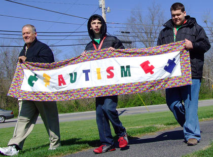 From left, Mike Higdon, Evan Martin, and Trent Higdon carried the banner to lead the ceremonial lap around the park to kick off the Working the Puzzle for Autism Walk.
