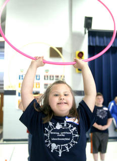 Kayla Garrett of Lebanon Elementary holds a hula hoop over her head to celebrate her team&#039;s win in a hula hoop relay.