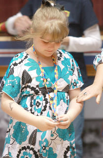 Aubrey Young of Campbellsville admires the medal she received at the start of the program. Twenty children with autistic spectrum disorders were recognized at the start of the event and presented with a medallion.