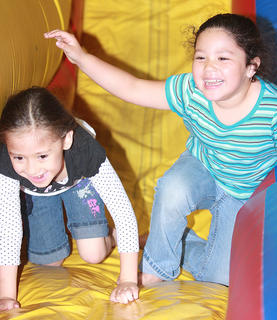 Shania Nava, 5, and Ashley Gonzalez, 5, both of Lebanon, couldn't help laughing after a trip down the bouncy slide together.