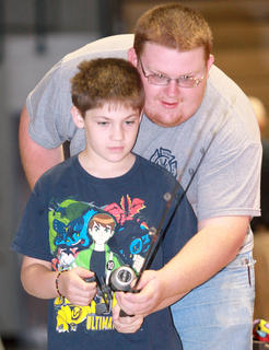 Parker Reid, 9, of Lebanon gets some fishing tips from his uncle, James Woodrun.
