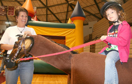 Jacklyn Farmer, 5, of Lebanon tries out a horse under the happy watch of Marchetta Garrison of the Reath Center in Campbellsville, which offer therapeutic horse riding.