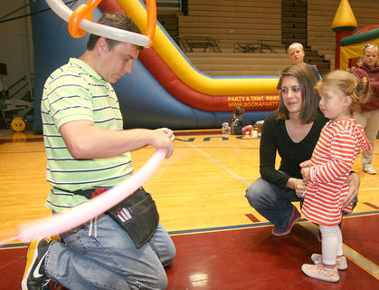 Jeff Wyman prepares to make a balloon pig for Olivia Gribbins, 2, of Lebanon and her mother, Andrea.
