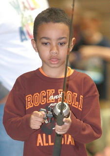 Kaden King, 6, of Lebanon is focused on reeling in something at the Fishing 4 Kids station.