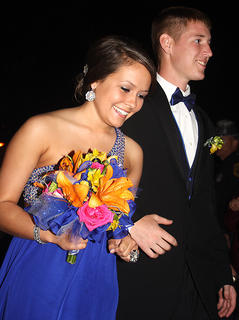 Lauren Brussell carries her bright, beautiful bouquet of flowers as she and her date, Ryan Peterson, arrive to the prom.