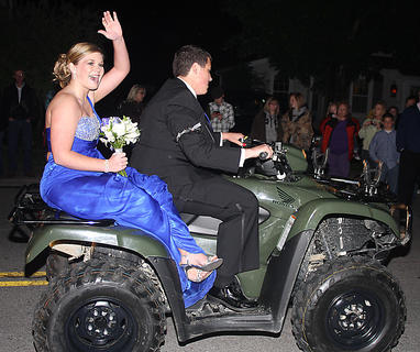 Emily Robey waves to the crowd as she and Kyle Gootee arrive to prom on a 4-wheeler.