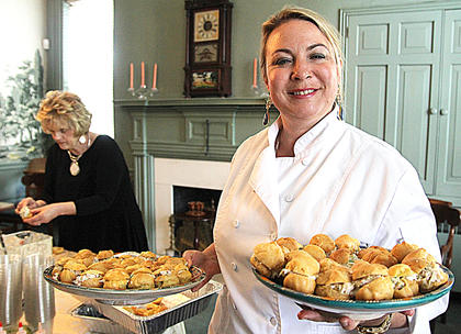 Chef Gwyn Artz prepares to deliver a tray of treats as Wanda Buckler helps to fix food in the background.