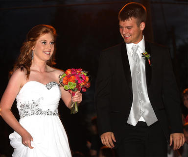 Courtney Bartley holds up her dress and walks carefully into prom as her date Dallas Smith admires her flowers.