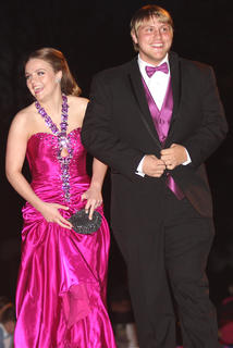 Chelsie Wright laughs with someone in the crowd of spectators as she and her date, Levi Brahm, walk into prom.
