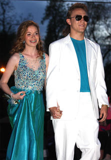 Lauren Pulliam smiles at the crowd gathered to watch students enter the prom while her date, Codhi Logsdon, looked like he walked right out of the Miami Vice television show.