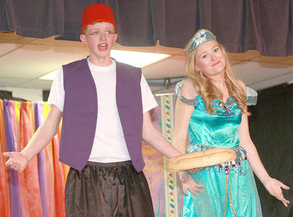 In the marketplace, Princess Jasmine (Carly Mattingly) meets Aladdin (Luke Jones), who stole a loaf of bread to eat.