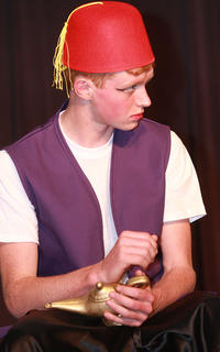 After being banished to a cave, Aladdin (Luke Jones) rubs a lamp and releases the genie inside.