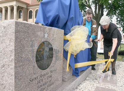 Sr. Sharon Sullivan and Sr. Mary Lois Speaks (right) unwrap the memorial commemorating the Ursuline Sisters of Mt. St. Joseph for 100 years of service in Marion County.