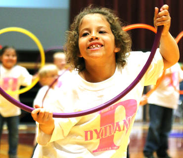 Naomi Huffman smiles through her hula hoop as she performs.