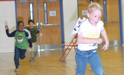Thomas Carrico pulls away for a win in a race of kindergartners, as Jamarion Calhoun and Samuel Cruz make the final turn.