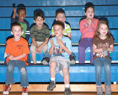 Kindergartner cheer on their classmates. On the top row are Jamarion Calhoun, Samuel Cruz, Aiden Forbes and Peyton Ervin. Christopher Orberson, Wesley Hayes and Kansas Hill are on the bottom row.