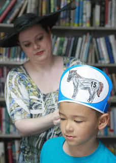 Children's Librarian Patty May Brown helps Cash Taylor make sure his Derby hat is the right size.