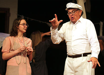 Mike Thacker, right, plays the part of Mr. Bundles, the laundry man, who comes in to the orphanage to pick up the blankets. While Miss Hannigan, played by Katie Vargo, is flirting with him, Annie climbs into the laundry basket and the orphans cover her up with the blankets. Annie successfully escapes the orphanage.