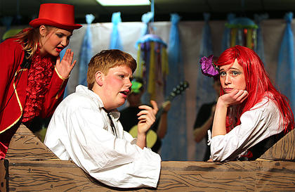 Sebastian, played by Shelby Hayden, left, tries to convince Prince Eric, played by Zachary Mullins, to kiss Ariel, played by Jessica Thomas.