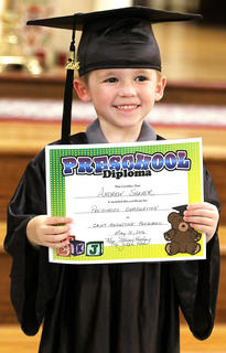 Andrew Shaver proudly holds up his preschool diploma and poses for photos.