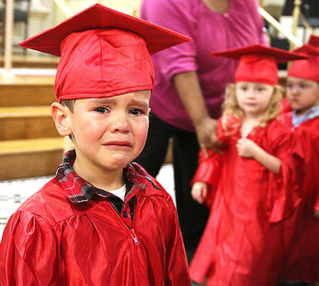 Carter Sapp just wasn't feeling it Thursday at the graduation ceremony. He was more interested in spending time with his momma. Also pictured is Madison Sizemore.