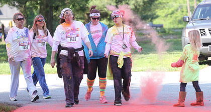 Participants get sprayed with a blast of color from one young volunteer.